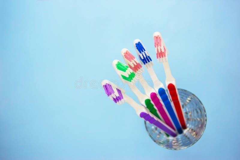 Зубные щетки в стеклянной, голубой предпосылке стоковое изображение rf