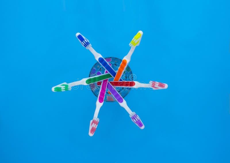 Зубные щетки в стеклянной, голубой предпосылке стоковое фото rf