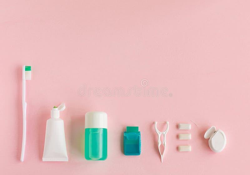 Зубные щетки, зубная паста, rinse и жевательная резина установили на розовую предпосылку стоковая фотография