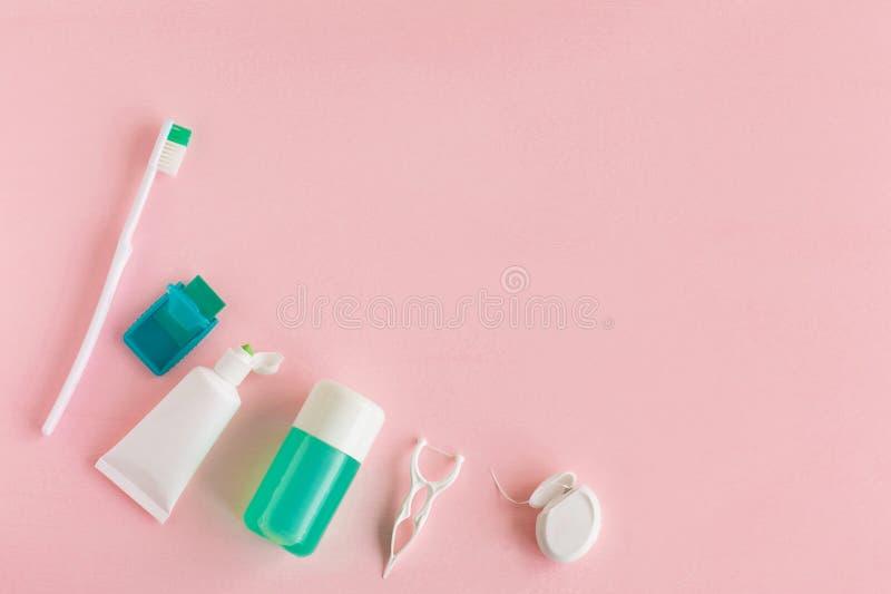 Зубные щетки, зубная паста, rinse и жевательная резина установили на розовую предпосылку стоковые изображения rf