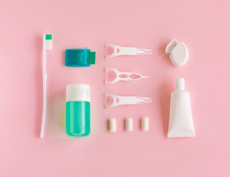 Зубные щетки, зубная паста, rinse и жевательная резина установили на розовую предпосылку стоковое изображение