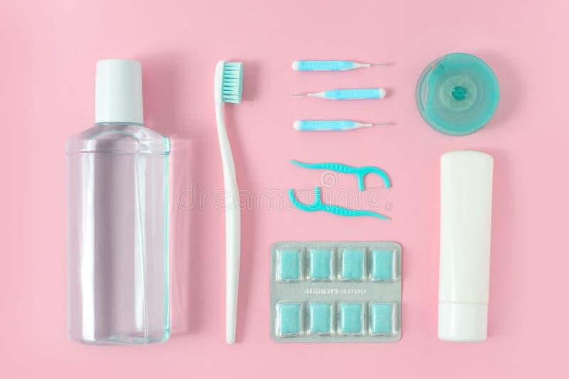 Зубные щетки, зубная паста, rinse и жевательная резина установили на розовую предпосылку Концепция зубоврачебных и здравоохранени стоковые фото
