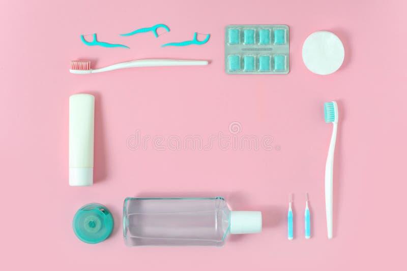 Зубные щетки, зубная паста, rinse и жевательная резина установили на розовую предпосылку Концепция зубоврачебных и здравоохранени стоковая фотография