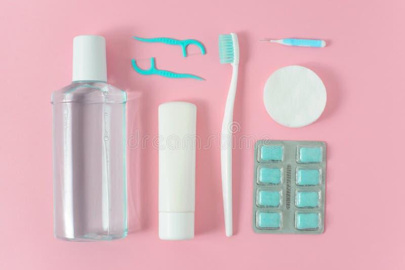 Зубные щетки, зубная паста, rinse и жевательная резина установили на розовую предпосылку стоковое фото