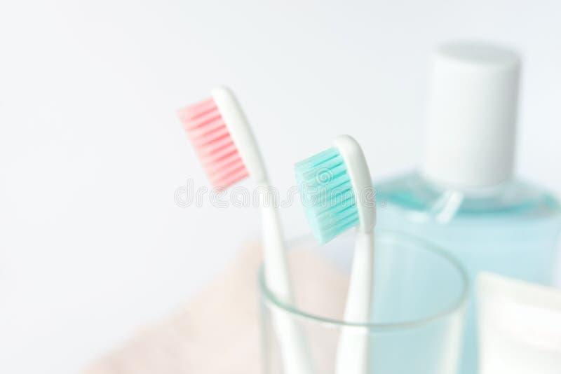 Зубные щетки, зубная паста, rinse и полотенце на белой предпосылке стоковые фото