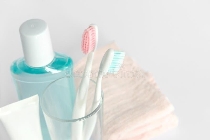 Зубные щетки, зубная паста, rinse и полотенце на белой предпосылке d стоковые фото