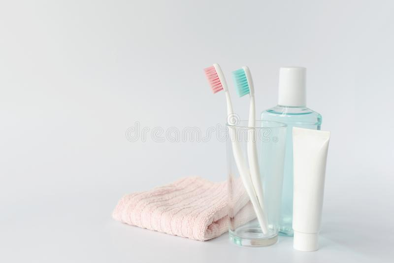 Зубные щетки, зубная паста, rinse и полотенце на белой предпосылке d стоковое фото rf