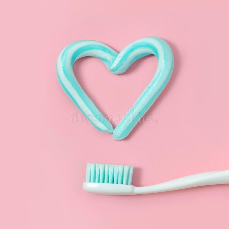 Зубные щетки и бирюза красят зубную пасту в форме сердца на розовой предпосылке стоковая фотография rf