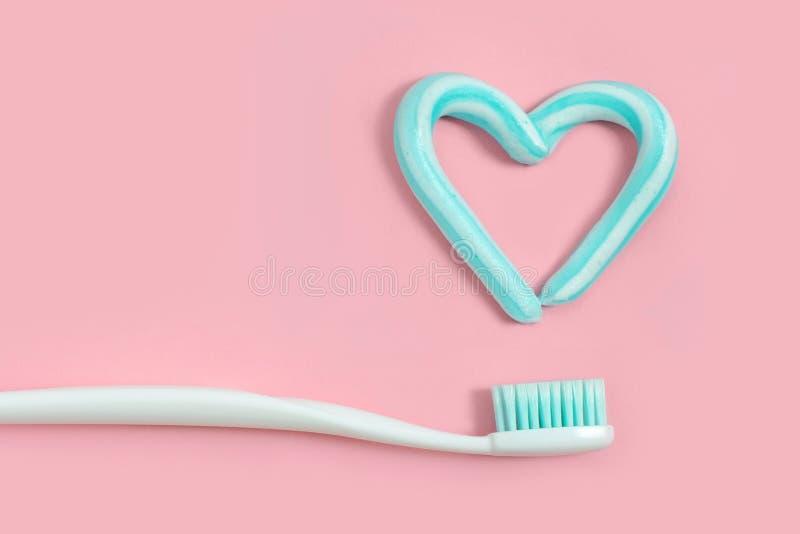 Зубные щетки и бирюза красят зубную пасту в форме сердца на розовой предпосылке Концепция зубоврачебных и здравоохранения стоковые изображения rf