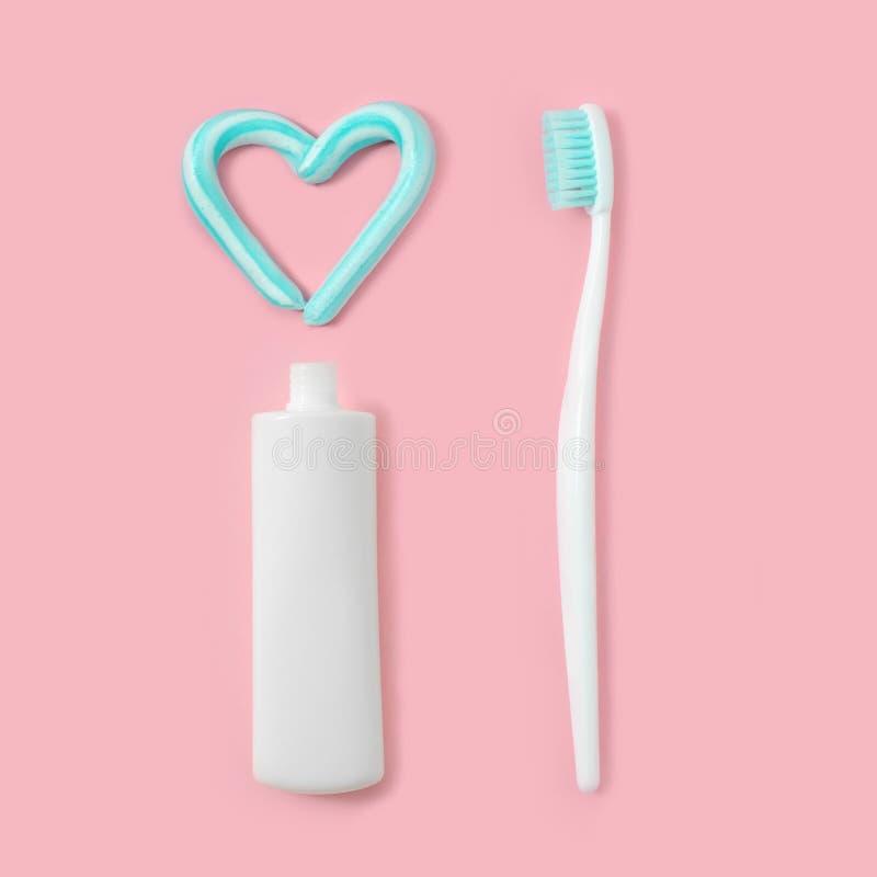 Зубные щетки и бирюза красят зубную пасту в форме сердца на розовой предпосылке Концепция зубоврачебных и здравоохранения стоковые изображения