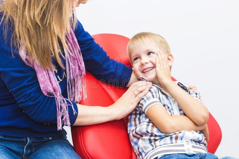 Зубоврачебная клиника Прием, рассмотрение пациента Забота зубов Мальчик с его матерью сидит в зубоврачебном стоковое изображение rf