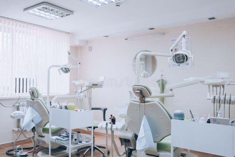 Зубоврачебный дизайн интерьера клиники со стулом и инструментами нескольких дантистов Современный зубоврачебный офис клиники с зе стоковая фотография