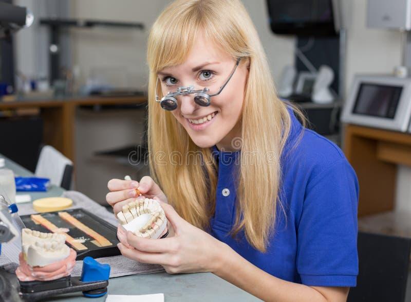 Зубоврачебный техник лаборатории прикладывая фарфор к прессформе зубной формулы стоковое изображение
