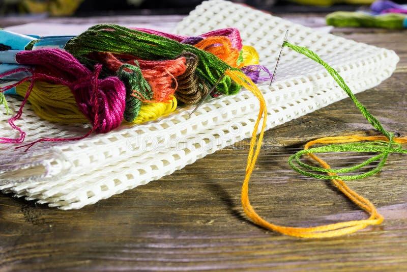 Зубочистка других цветов лежа на большом холсте вставила ее с иглами Деревянная деревенская таблица стоковое фото