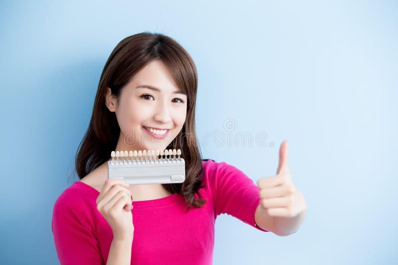 Зубы владением женщины забеливая инструмент стоковое фото