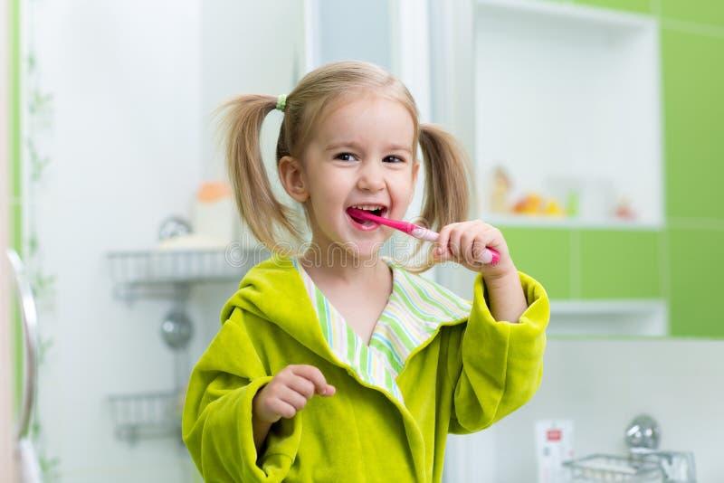 Зубы девушки маленького ребенка чистя щеткой в ванне стоковое изображение rf