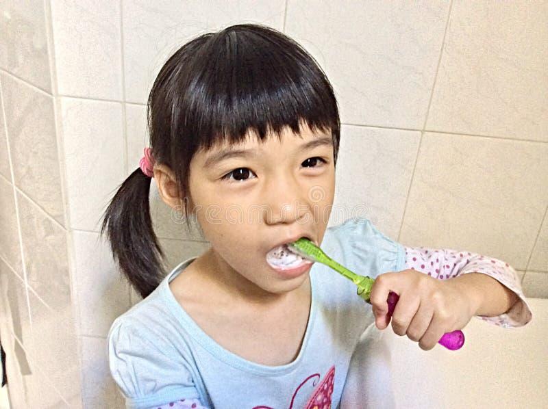 Зубы девушки чистя щеткой стоковые фото