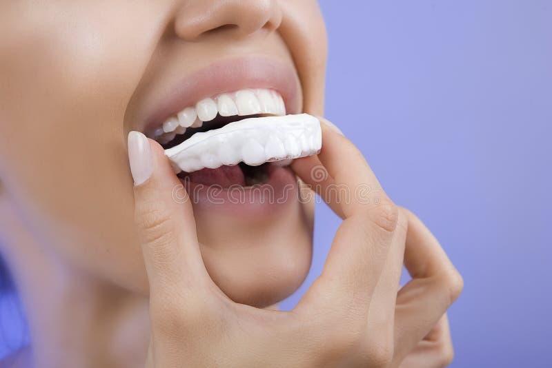 Зубы забеливая - усмехаясь девушка с подносом зуба, концом-вверх стоковые изображения