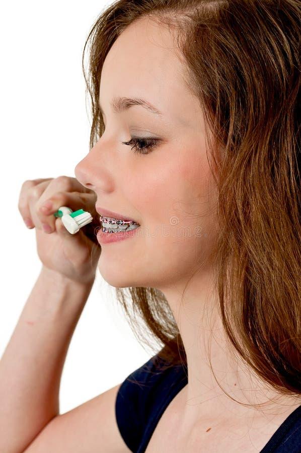Зубы красивой подростковой женщины чистя щеткой стоковая фотография rf