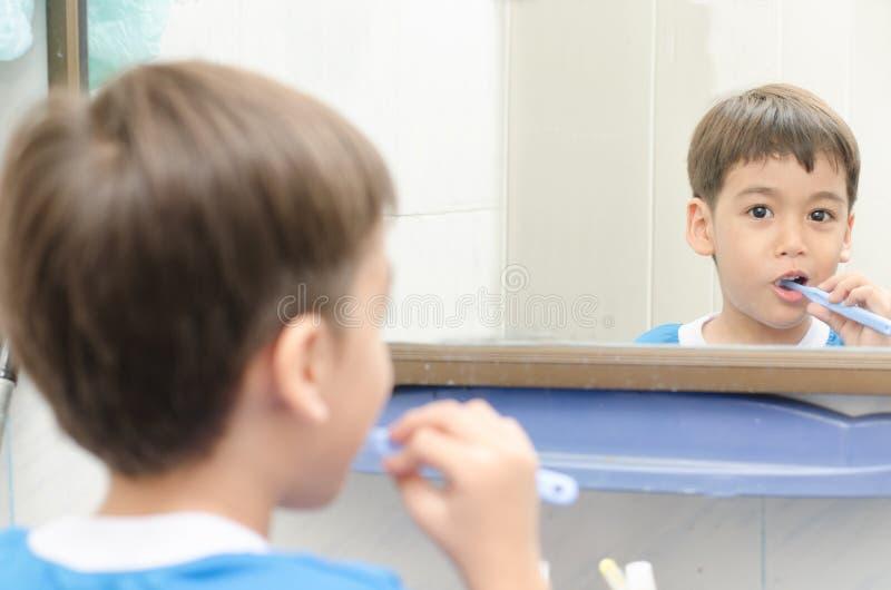 Зубы мальчика чистя щеткой смотря на heathcare зеркала зубоврачебном стоковая фотография rf