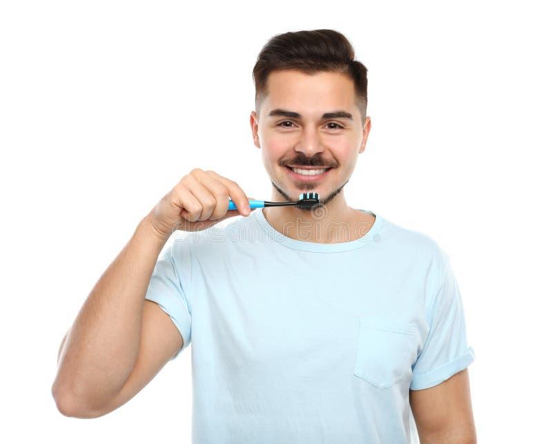 Зубы молодого человека чистя щеткой на белизне стоковое фото