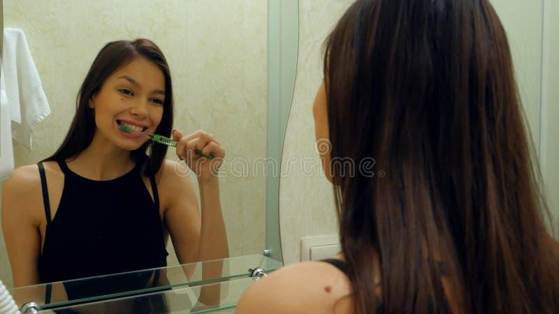 Зубы молодой красивой кавказской женщины брюнет чистя щеткой и усмехаться в зеркале стоковое изображение