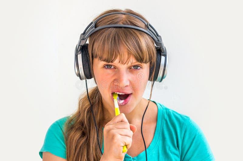 Зубы молодой дамы чистя щеткой в утре стоковые изображения