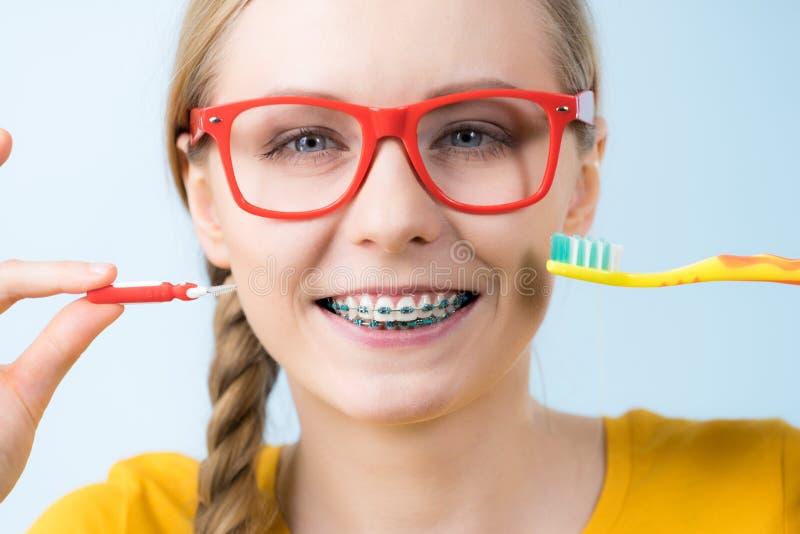 Зубы чистки женщины усмехаясь с расчалками стоковая фотография rf