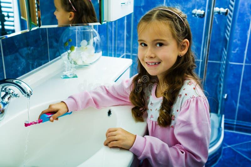 Зубы 2 девушки чистя щеткой стоковая фотография