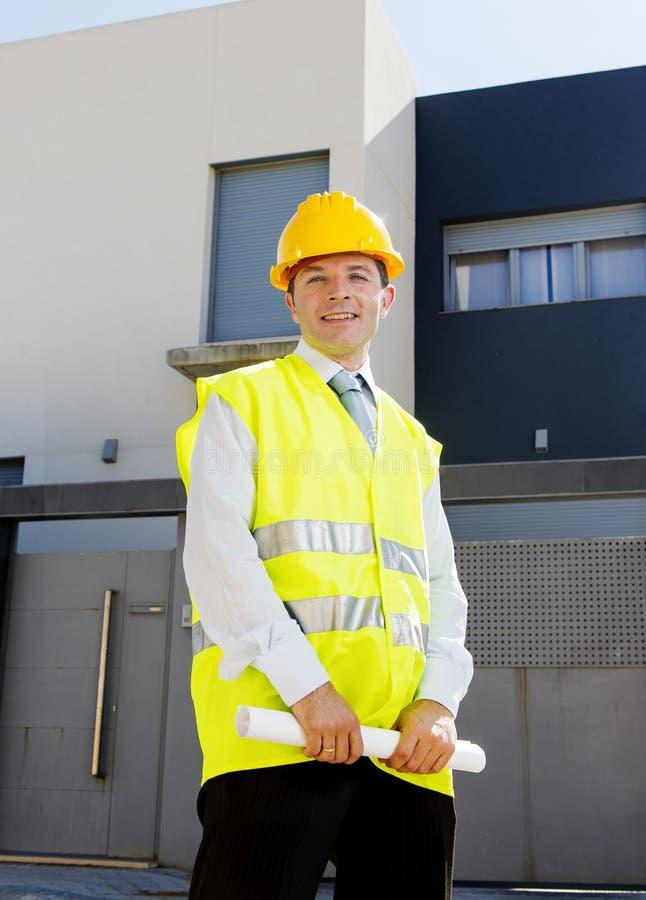 Здание молодого привлекательного работника мастера наблюдая blueprints outdoors нося шлем конструкции стоковые изображения rf