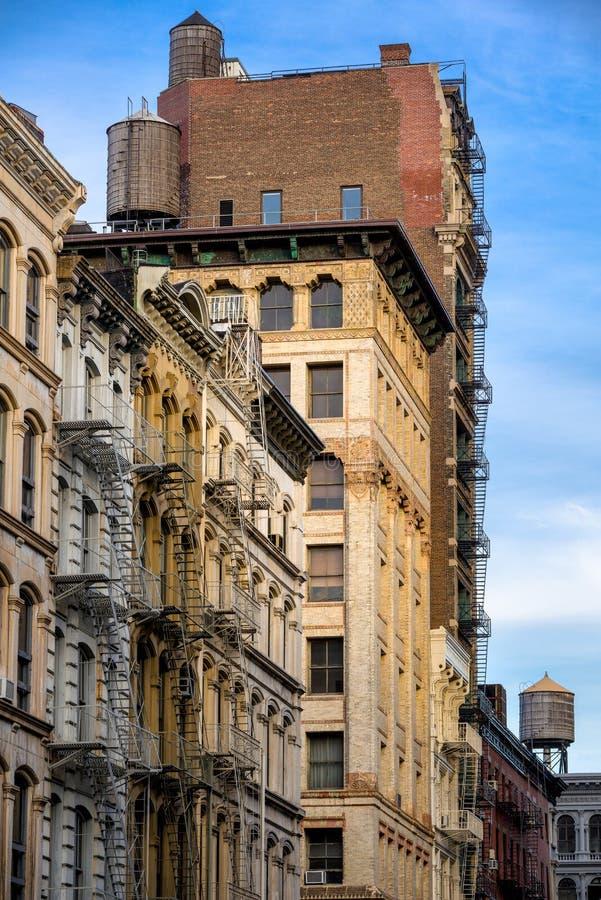 Здания просторной квартиры Soho с пожарной лестницей и водонапорными башнями, Манхаттаном стоковые изображения