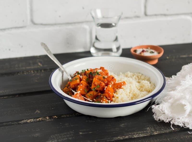Здоровая еда - тушёное мясо и кускус тыквы в белом шаре эмали на темной деревянной доске Вегетарианский обед стоковое изображение rf