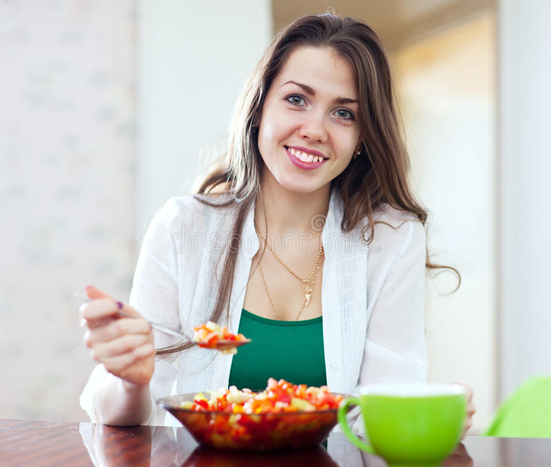 Здоровая женщина есть салат veggie с ложкой стоковые изображения