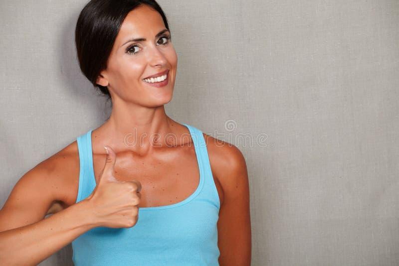 Здоровая женщина с большим пальцем руки поднимающим вверх и усмехаться стоковое фото