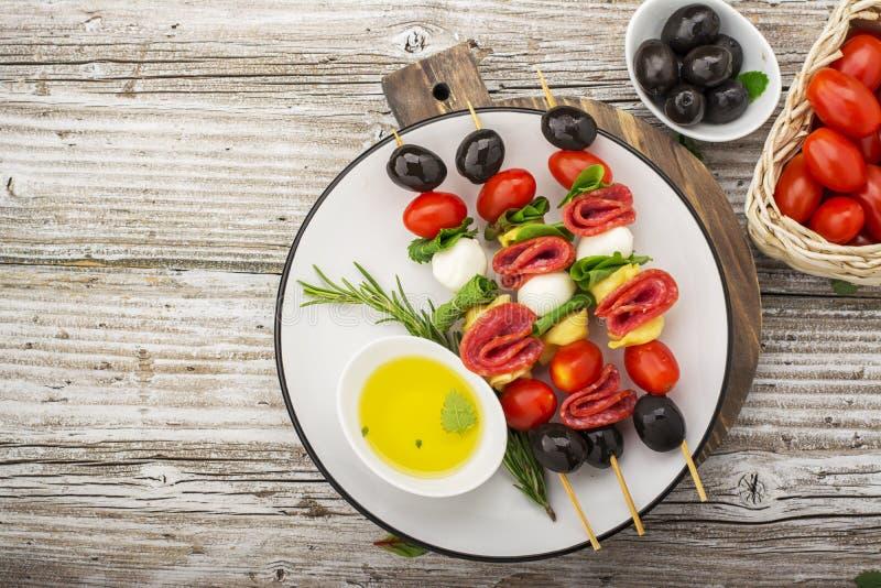 Здоровая закуска: рт-моча kebabs на пикнике с томатами, моццарелле, салями, черных оливках, базилике, tortellini стоковое фото rf