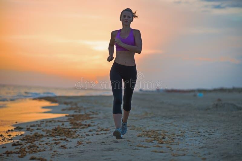 Здоровая молодая женщина бежать на пляже в вечере стоковое изображение
