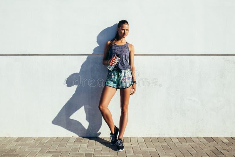 Здоровая молодая женщина отдыхая после разминки стоковые изображения rf