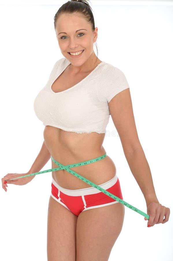 Здоровая счастливая довольная молодая женщина проверяя ее потерю веса с рулеткой стоковые изображения rf