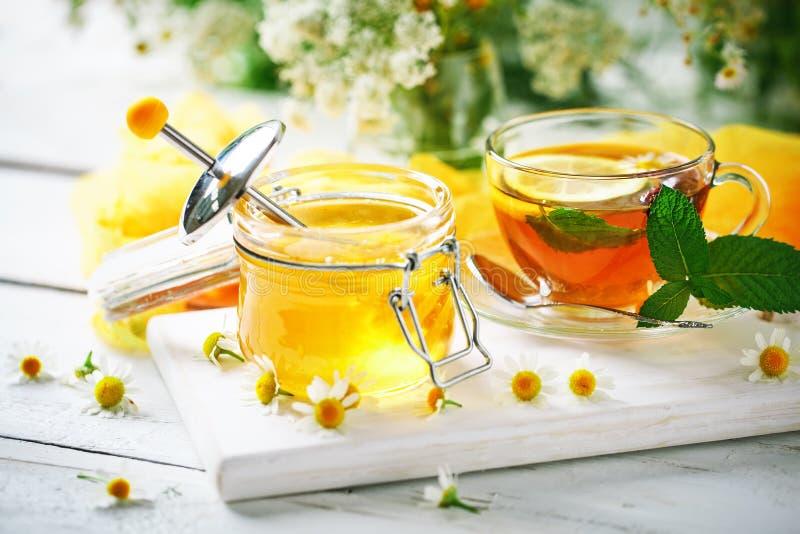 Здоровая чашка чаю, опарник меда и цветки Селективный фокус стоковые изображения rf