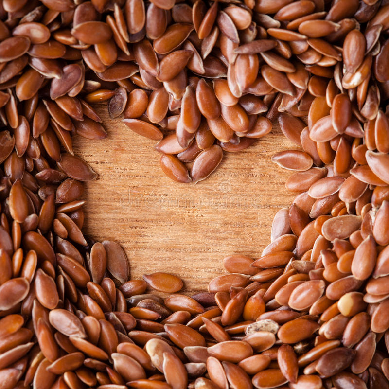 Здоровое питание. Граница льняного семени семян льна на деревянной предпосылке стоковое изображение