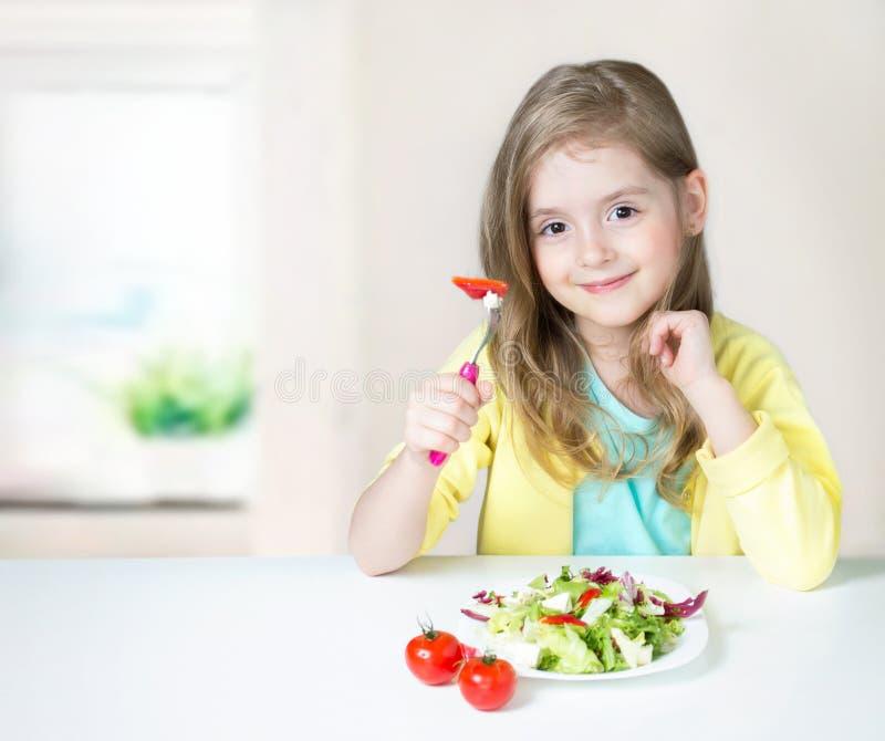 Здоровое питание ребенка Девушка есть салат на таблице стоковые фотографии rf