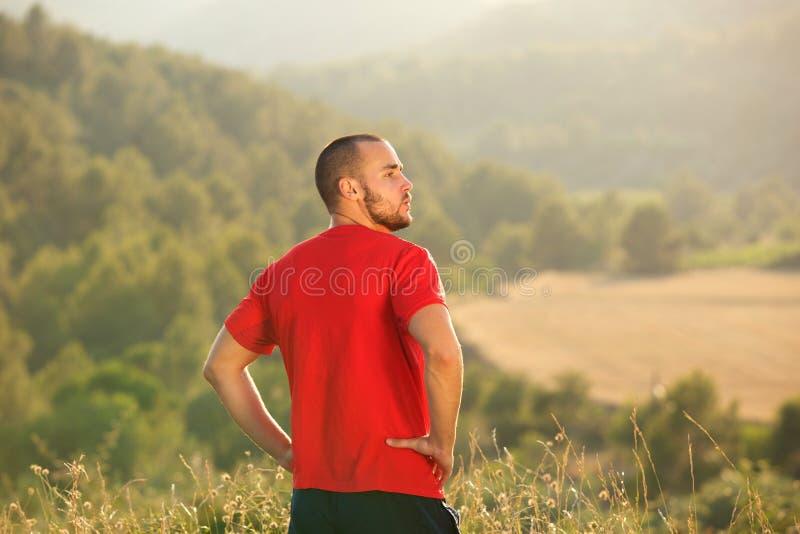 Здоровое снаружи молодого человека стоящее в природе стоковое фото rf