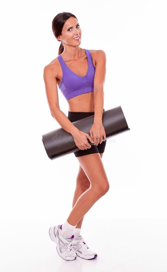 Здоровое усмехаясь брюнет держа циновку йоги стоковая фотография rf