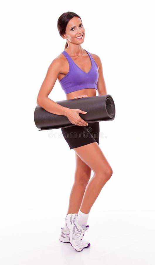 Здоровое усмехаясь брюнет держа циновку йоги стоковые фотографии rf