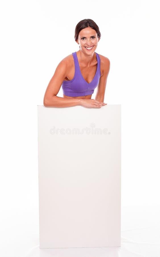 Здоровое усмехаясь брюнет за пустым плакатом стоковое изображение