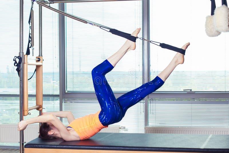 Здоровое усмехаясь трико женщины нося практикуя Pilates в яркой студии тренировки стоковое фото