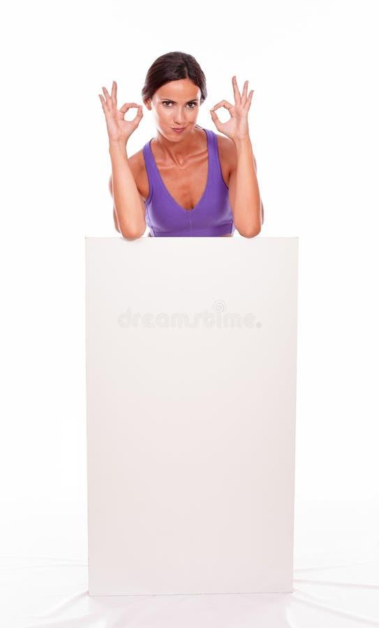 Здоровое pouting брюнет за пустым плакатом стоковые фотографии rf