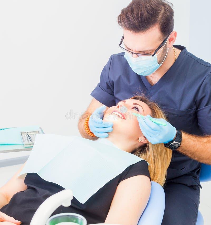 Здоровые зубы терпеливые на предохранении зубоврачебной костоеды офиса дантиста стоковая фотография rf