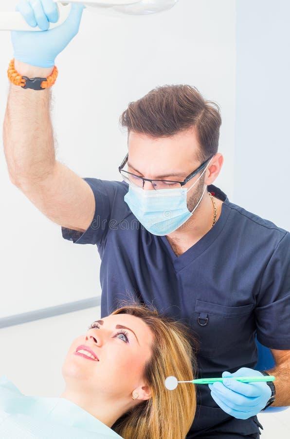 Здоровые зубы терпеливые на предохранении зубоврачебной костоеды офиса дантиста стоковое фото rf