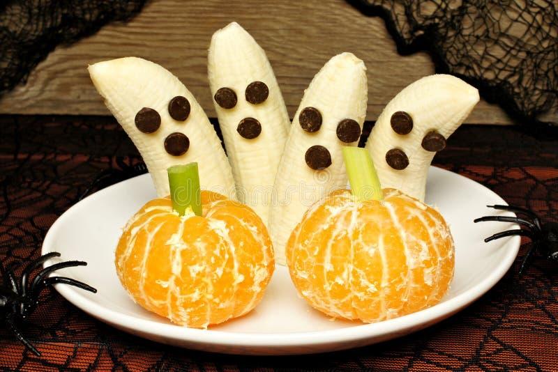 Здоровые призраки банана хеллоуина и оранжевые тыквы стоковая фотография